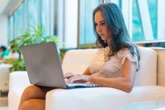 Young woman sitting on sofa at hotel lobby working laptop computer Stock Photos