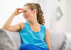 Young woman sitting on sofa and laughing Stock Image