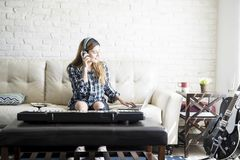 Woman music composer at home. Young woman sitting on sofa and listening music from laptop intend to practice compose her song royalty free stock photos