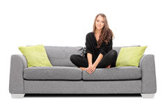Young woman sitting on a sofa and looking in the camera Stock Photos