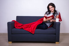 Young woman sitting on sofa with mug of tea and book wrapped in Royalty Free Stock Image