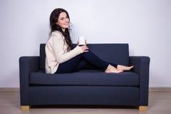Young woman sitting on sofa with mug of tea or coffee Stock Photos