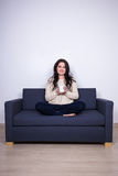 Young woman sitting on sofa with mug of tea at home Stock Photo