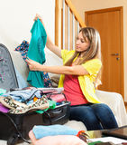 Young woman sitting on a sofa near the open suitcase Stock Photos