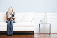 Young Woman Sitting on Sofa Reading Stock Image