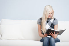 Young Woman Sitting on Sofa Reading Book Royalty Free Stock Photography