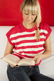 Young woman sitting on a sofa reading book Royalty Free Stock Images
