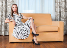 Young woman sitting on sofa Stock Images