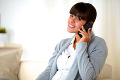 Young woman sitting on sofa speaking at cellphone Stock Photo