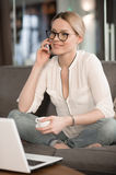 Young woman sitting on sofa, talking on phone and smiling. Business negotiations. Talking of phone Stock Image