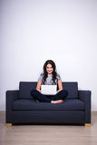 Young woman sitting on sofa and using laptop at home Stock Images