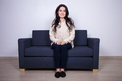 Young woman sitting on sofa and watching tv. Young beautiful woman sitting on sofa and watching tv Royalty Free Stock Photo