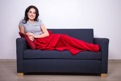 Young woman sitting on sofa wrapped in red blanket Stock Image