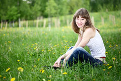 Young woman sitting on spring meadow smiling. Royalty Free Stock Photos