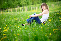 Young woman sitting on spring meadow smiling. Stock Image