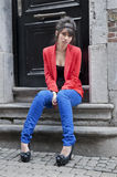 Young woman sitting on stairs in a door way Royalty Free Stock Photography