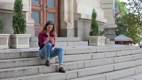 Young woman sitting on stairs at entrance to building and looking at smartphone stock video footage