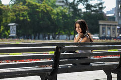 Young woman sitting on the stairs and listening to music. Young girl sitting on the stairs near the university and listening to music Stock Photo