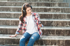 Young woman sitting on stairs listening to music on headphones Royalty Free Stock Photo