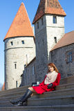 Young woman sitting on stairs in old town Royalty Free Stock Photos