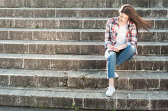 Young woman sitting on stairs in the park and writing Royalty Free Stock Photo