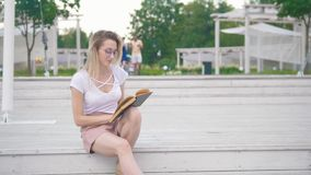 Young woman sitting on the stairs reading a book in the urban park. Close up stock video footage