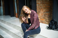 Young pretty woman sitting on stairs and use phone with big smile in city street Stock Images