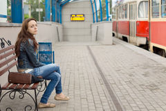 Young woman sitting on a station platform Royalty Free Stock Image