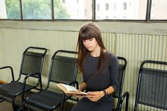 Young woman sitting at the station reading a book stock photography