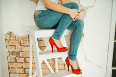 Young woman sitting on a stepladder Stock Image