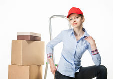 Young woman sitting on the stepladder near the stack of boxes Royalty Free Stock Photos
