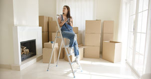 Young woman sitting on a stepladder Royalty Free Stock Photos