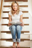 Young woman sitting on steps. Pretty young smiling woman sitting on steps at home Royalty Free Stock Images