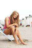 Young woman sitting on steps at the beach with barefeet in sand. Portrait of a cute young woman sitting on steps at the beach with barefeet in sand Stock Photo
