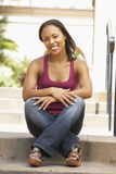 Young Woman Sitting On Steps Of Building Royalty Free Stock Image