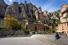 Young woman is sitting on steps among buildings of Montserrat monastery located between huge rocks in Catalonia, Spain Stock Photos