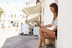 Young woman sitting on steps looking at her phone, side view Royalty Free Stock Images