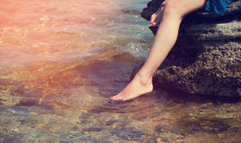 Young woman sitting on a stone, dropped feet into the sea water. Young woman sitting on the stone, put his feet in clean and clear sea water. Sunny day. The Stock Image