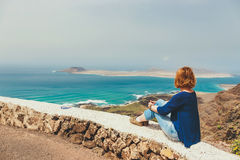 Young woman sitting on stone fence. Looking at sea Royalty Free Stock Photos
