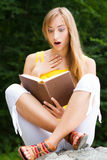 Young woman sitting on a stone,reading a book Stock Photography