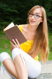 Young woman sitting on a stone and reading a book Stock Image