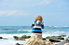 Young woman sitting on the stone on the seashore Stock Photo