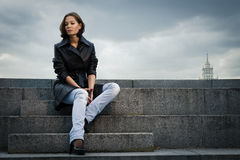 Young woman sitting on stone steps Stock Photo