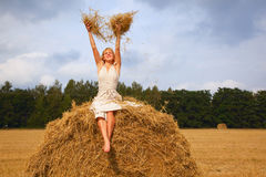 Young woman is sitting on a straw Royalty Free Stock Photos