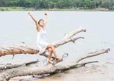 Young woman sitting stretch her hands on tree trunk at lake and Stock Photo