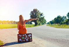 Young woman sitting on suitcase and hitchhiking. Picture of young woman sitting on suitcase on country crossroad. Backview of blond girl in orange dress Stock Photo
