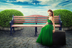 Young woman sitting on a suitcase waiting for a ride Stock Photo