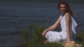Young woman sitting in a summer dress on the riverbank and enjoy the summer day.  stock video