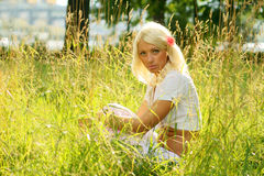 Young woman sitting on a summer meadow Royalty Free Stock Images