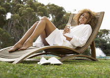 A young woman sitting on a sun lounger royalty free stock photography